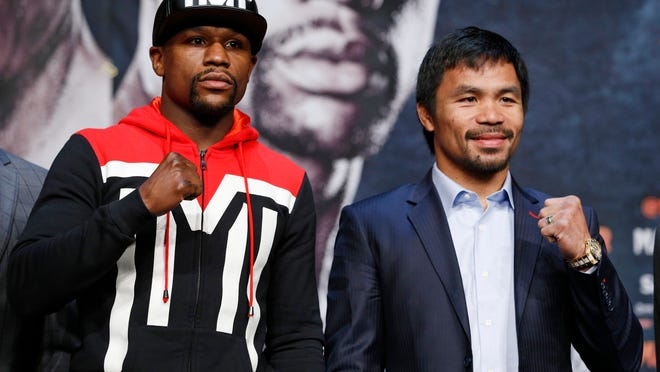 Boxers Floyd Mayweather Jr., left, and Manny Pacquiao pose for photographers during a press conference Wednesday, April 29, 2015, in Las Vegas. The pair are slated to square off Saturday in Las Vegas. (AP Photo/John Locher)