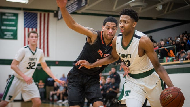 Trinity's David Johnson (13) drives to the basket around Fern Creek's Ahmad Price (10) during the game at Trinity High School in Louisville, Kentucky, Saturday, December 9, 2017
