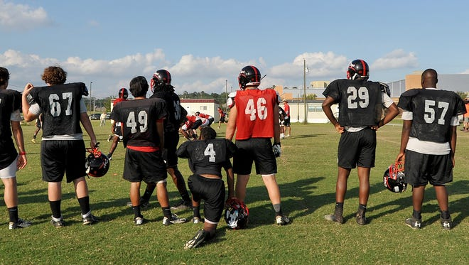 Brandon High School players watch from the sidelines during practice at the school.