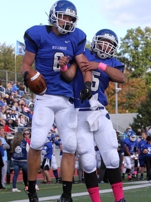 The Blue Jays of  Middlesex High School take on the Bulldogs of Metuchen High School in a varsity football game on Saturday October 17,2015.Metuchen's # 6 (left)- Trevor Firgau celebrates his first half touchdown with team mate # 4 (right)- Jake Lebovits.