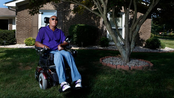 Cleveland Graham sits in front of his home, which Citibank is trying to foreclose on.  Graham is a paraplegic Vietnam veteran whose ex-wife borrowed against his home without his knowledge. Sept. 16, 2015.