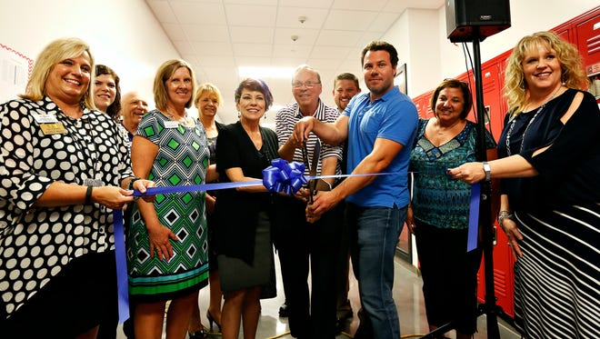 Members of the Springfield Chamber of Commerce, the New Covenant Academy school board and the Coryell family cut a ribbon during the opening ceremony for the Coryell Intermediate Wing of New Covenant Academy in Springfield, Mo. on Aug. 12, 2016.