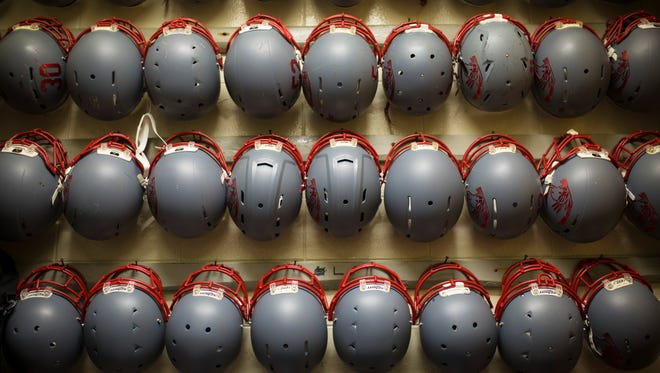 Football helmets hang on the wall inside an equipment room at Waggener Traditional High School. Nov. 18, 2016