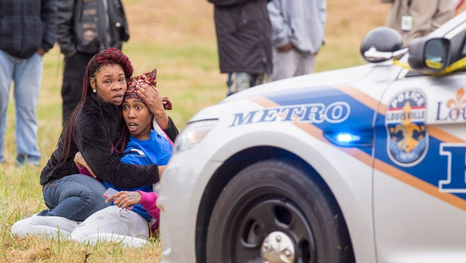 A woman is restrained after reacting to knowing a shooting victim after six were shot, with two dead, following a shooting on Thanksgiving Day at Shawnee Park during the annual Juice Bowl event. Nov. 24, 2016