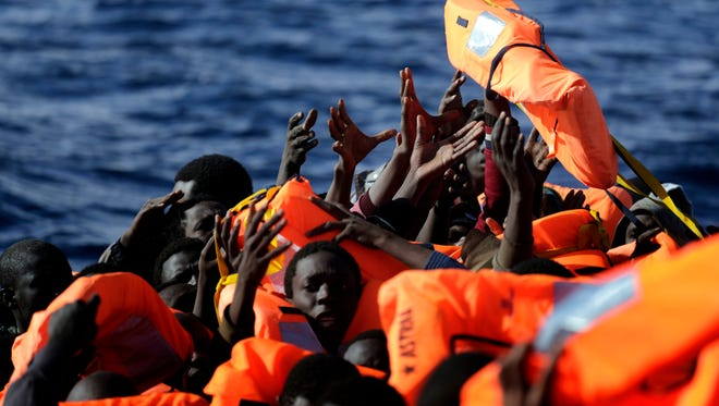 Sub-Saharan migrants raise their hands to grab a life jacket as they are rescued by members of the Proactive Open Arms NGO, in the Mediterranean Sea north of Zumarah, Libya, on Jan. 27, 2017.