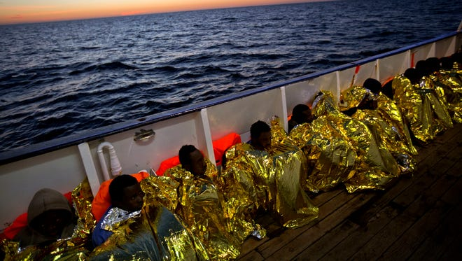 Wrapped in blankets, Sub-Saharan migrants sit on the deck of the ship Golfo Azzurro after their rescue from a rubber boat by members of the Proactive Open Arms organization in the Mediterranean sea, about 24 miles north of Sabratha, Libya, on Jan. 27, 2017.