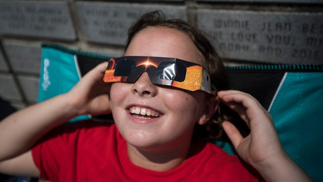A child tries on a pair of eclipse glasses at the Jefferson Cross Memorial Park in Wickliffe, Ky. Aug. 21, 2017