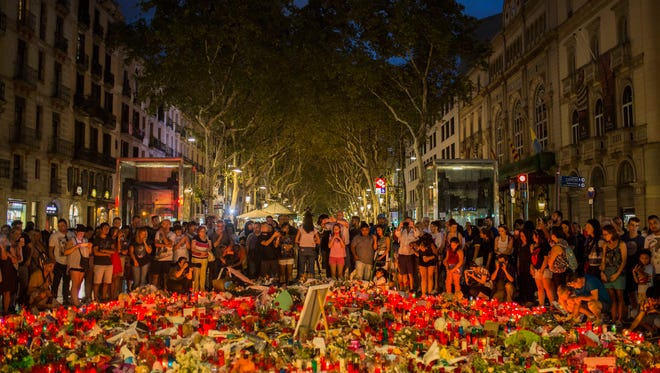 People stand next to candles and flowers placed on the ground, after a terror attack that left many killed and wounded in Barcelona, Spain on Aug. 20, 2017.