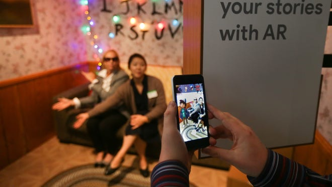 Attendees demo the augmented reality integration of the new Google Pixel 2 smartphone. Improved cameras on smartphones are flooding our digital accounts with snapshots.