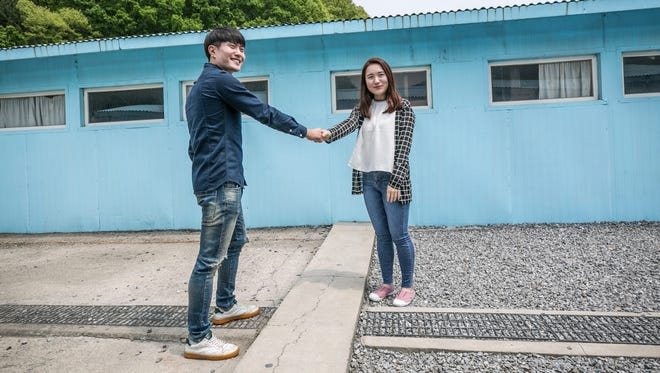 Visitors mimick the two Korean leaders by shaking hands as they take pictures at a mock Panmunjeom May 5, 2018 in Namyangju, South Korea.