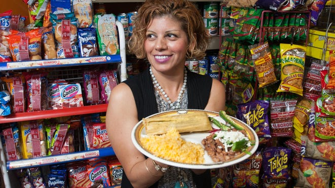 Tortilleria La Rancherita owner Yesenia Judice holds a plate with a tamale made in her restaurant in Bonita Springs, FL on Thursday, December 10, 2015. The restaurant plans on making more than 1,000 handmade tamales for its clientele this Christmas season.