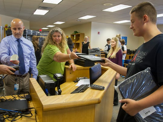 Joshua Darrell, 13, right, an 8th grader at Challenger Middle School in Cape Coral, receives his school-issued Chromebook laptop from staffer Kelly McGuire during the first day of classes Wednesday, August 10.  Superintedent Greg Adkins was visiting the school and assisted in the process.