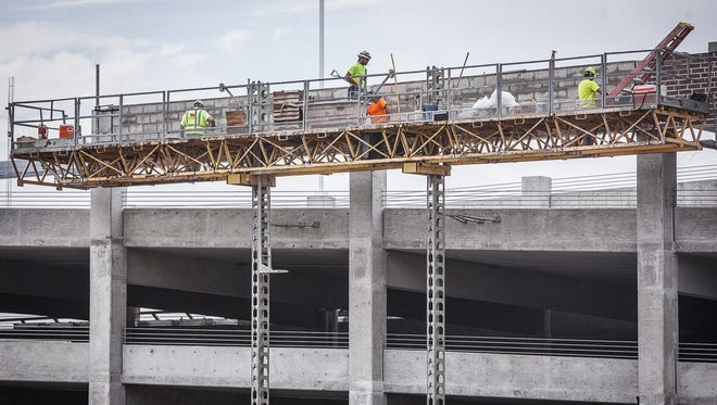 A construction crew works on the downtown parking garage located behind the future site of the Arc hotel in June.