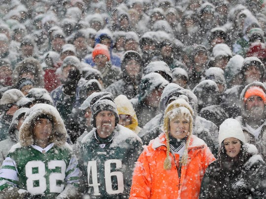 Fans watch the Philadelphia Eagles play the Detroit Lions as snow falls during first-quarter NFL football game action on Sunday, Dec. 8, 2013, in Philadelphia. (AP Photo/Philadelphia Inquirer, Yong Kim) PHILADELPHIA OUT; NEWARK, N.J. OUT; TV OUT; MAGAZINES OUT ORG XMIT: PAPHQ902
