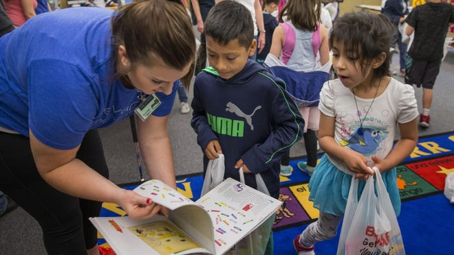 Elizabeth Gray (left) helps students pick out a book during BookFest at Guy Lee Elementary School in Springfield in 2018. The book giveaway is a collaboration of United Way of Lane County, the Early Learning Alliance and Connected Lane County. [Chris Pietsch/The Register-Guard file] - registerguard.com