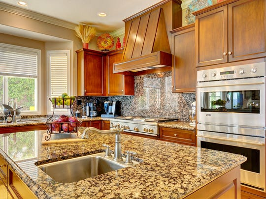 The kitchen is a gourmet cook's dream, with a breakfast area, wood cabinetry with pullout shelving, granite countertops, stainless steel appliances and an island with its own sink and trash compactor.