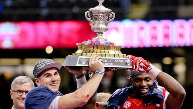 Jan 1, 2016; New Orleans, LA, USA; Mississippi Rebels quarterback Chad Kelly and wide receiver Laquon Treadwell celebrate by holding up the Sugar Bowl trophy following a win against the Oklahoma State Cowboys in the 2016 Sugar Bowl at the Mercedes-Benz Superdome. Mandatory Credit: Derick E. Hingle-USA TODAY Sports