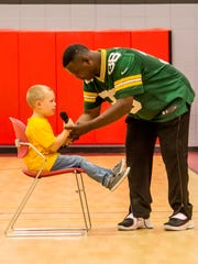 LeRoy Butler asks a student to hold his microphone during his presentation so that he can re-tie his shoe.