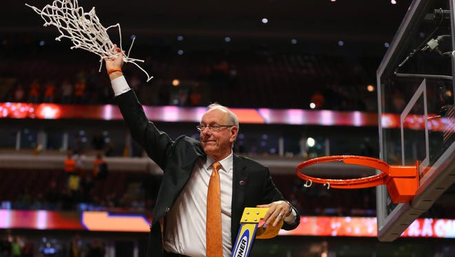 Syracuse Orange head coach Jim Boeheim waves to the crowd after cutting down the net.