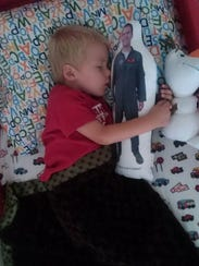 """Connor Willoughby, 3, sleeps with his """"Daddy doll"""""""