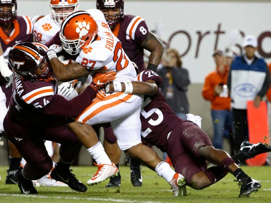 Clemson running back C.J. Fuller (27) powers in for a touchdown as Virginia Tech linebacker Andrew Motuapuaka (54) and safety Terrell Edmunds try to make the stop during the first half of an NCAA college football game in Blacksburg, Va., Saturday, Sept. 30, 2017. (AP Photo/Steve Helber)
