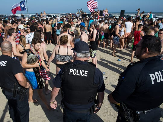Port Aransas police stand in the middle of a large crowd on the beach in Port Aransas during the first day for spring break on Saturday, March 10, 2018.