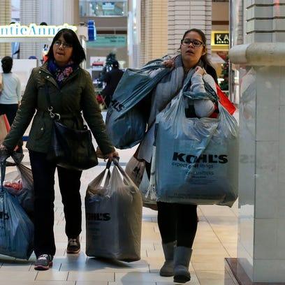 JERSEY CITY, NJ - NOVEMBER 27: Customers carry shopping