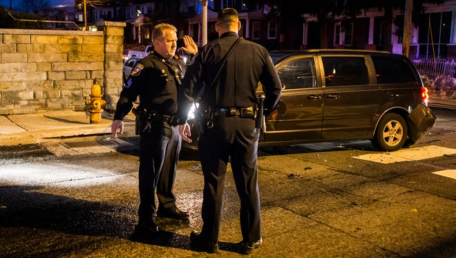 Sgt. Bill Schmid, of the Wilmington Police Department, explains to another officer how a motor vehicle collision occurred from witness statements after coming upon the vehicles while on patrol Sunday night, Dec. 18, 2016.