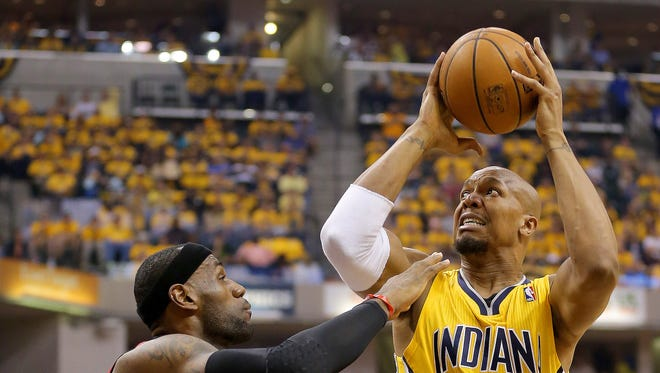 Pacers forward David West grimaces as he puts up a shot over Miami Heats forward LeBron James during the first half of action. Indiana Pacers play the Miami Heat in Game 1 of the NBA Eastern Conference Finals Sunday, May 18, 2014, afternoon at Bankers Life Fieldhouse.