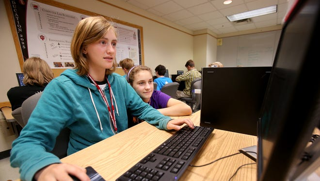 Sisters Maureen Lynch (left), 14, and Ada, 12, work on a puzzle game during Game Development Camp on July 15, 2014, at Indiana University in Bloomington.