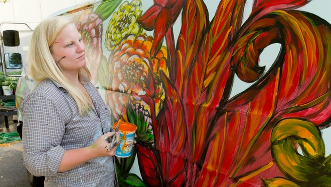Former Ithacan Kellie Cox-Brady of Silver Spring Md., examines her work late Friday afternoon as she nears completion of her mural on the Beautification Brigade's new van. The Cornell Cooperative Education of Tompkins County program plants and maintains the flowers around the City of Ithaca.
