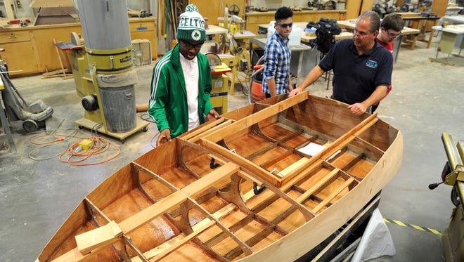 In this Dec. 2, 2013, photo, Justin Watts and Technical Education instructor Robert Larnerd look at one of the cocktail racing boats being built in the marine construction class at the Regional Aquaculture School, in Bridgeport, Conn.