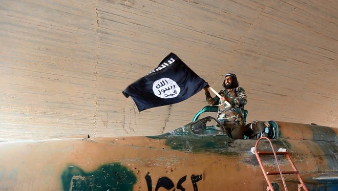 This undated image posted Aug. 27, 2014, by the Syrian opposition group Raqqa Media Center of the Islamic State shows an IS fighter waving the group's flag from inside a captured government fighter jet following the battle for the Tabqa air base on Sunday.