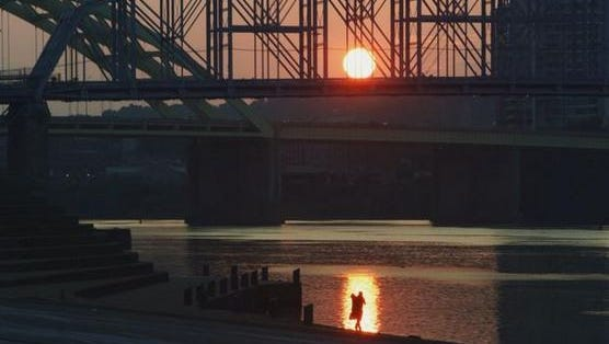 A person walks over the Public Landing as the sun rises over the Ohio River on Thursday morning.