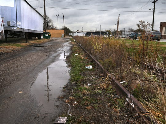 Selese Goss, 45, was found dead in this alley that runs East-West between the 2100 block of Columbia Street and Dr. Andrew J. Brown Avenue (background). The alley, shown on Thursday, Nov. 6, 2014, is adjacent to an abandoned Penn Central Railroad track.