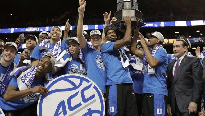 Duke players hold up the championship trophy after beating Notre Dame 75-69 in the Atlantic Coast Conference tournament chamnpionship game Saturday night.