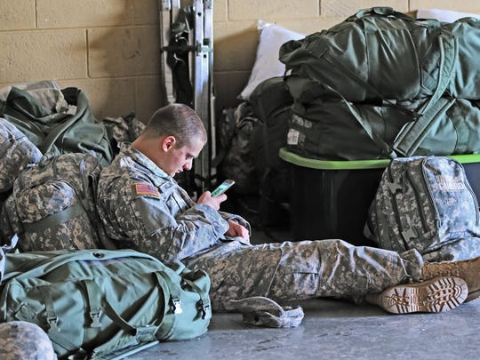 Spc. Daniel Millunzi checks messages on his phone while waiting for a truck to carry gear to Florida to aid in Hurricane Irma cleanup.