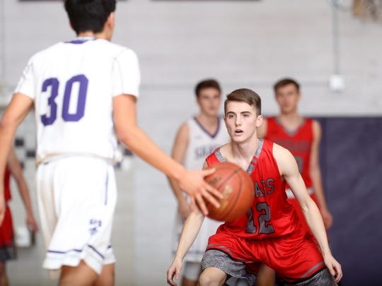 Foothill's Caden Campbell keeps an eye on Shasta's Stefan Goodman in the Cougars' 68-48 win.