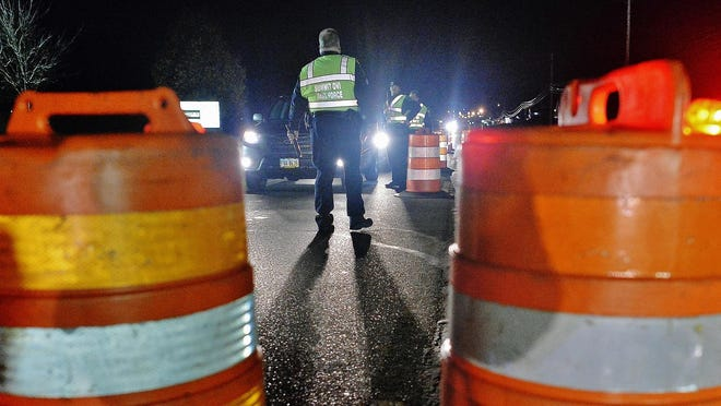 Sgt. Dan Drummond of the Stow Police Department approaches a vehicle at a sobriety checkpoint conducted Dec. 15 by the Summit County OVI Task Force on East Turkeyfoot Road in Green.