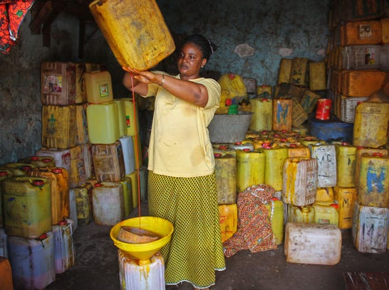 Palm oil vendor Pauline Haba pours palm oil from a container on Aug. 26. Her business is suffering because no one wants to buy her palm oil, which comes from an area where the Ebola outbreak has cost many lives in Conakry, Guinea.