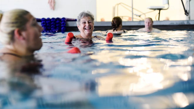 Carol Drueckhammer, center, chats with instructor and assistant aquatic director Serena Fisher during an arthritis class. 'We're working every joint in the body from their head to their feet,' Fisher said.