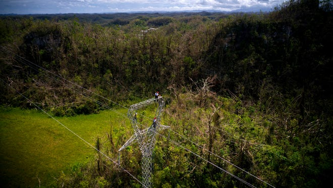 In this Oct. 15, 2017 file photo, electrical lineman work on transmission towers in Barceloneta, Puerto Rico. A small Montana company that landed and lost a contract to restore Puerto Rico's hurricane-shattered electric grid has reached a settlement in a dispute over money it said it was owed for the work. Representatives of Montana-based Whitefish Energy Holdings and Arc American of Indiana confirmed the settlement Wednesday, Dec. 6, 2017. They declined to release details.