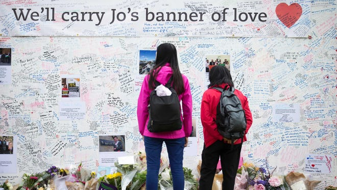 People look at a memorial to murdered Labour MP, Jo Cox is pictured outside the Houses of Parliament in London on June 20, 2016.