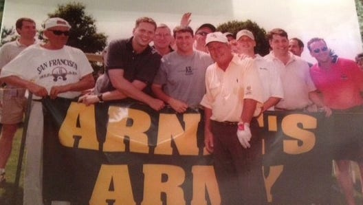 """Arnold Palmer poses with members of the Berl family and their friends who had made an """"Arnie's Army"""" sign for the Hillside Skills Challenge at Blue Heron Hills Country Club in Macedon in 1999. Pictured are, front, from left, Richard Berl, Jeff Berl, John Mills, Palmer, David Berl, Jay Koenig and Dan Berl."""