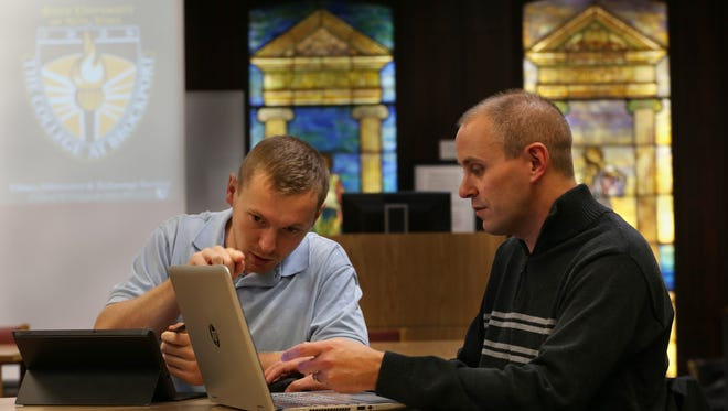 Brockport students Kevin Flynn and Larry Passantino, work on a presentation of an app they developed to help teach high schoolers learn math and science at The College at Brockport.