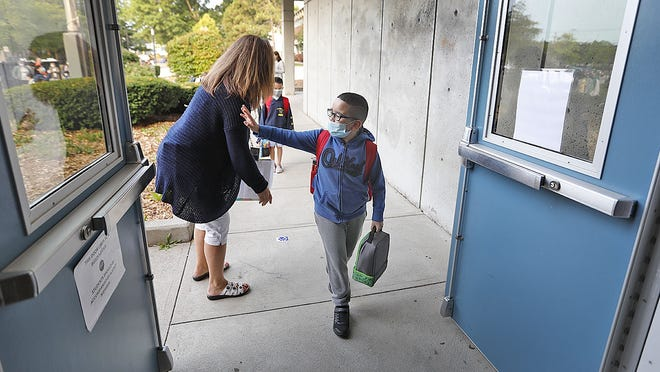 A second grader waves to his parents as he enters Lincoln-Hancock School in Quincy on Thursday, Sept. 17, 2020. Greg Derr/ The Patriot Ledger