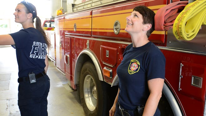 South Lyon Firefighters Brittany Tooman, left, and Cindy Conrad check out some supplies in an engine parked at Station #7 on Whipple St. on Aug. 22. The South Lyon City and Lyon Township fire departments may possibly merge services in the future.