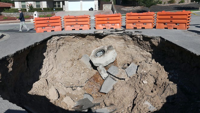 A nearby homeowner walks by a large sinkhole at La Placita and Villa Hermosa in West El Paso Sunday.