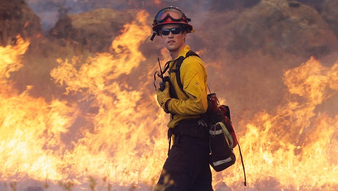 Garden Valley firefighter Chris Schwegler walks by flames along Morgan Valley Road near Lower Lake, Calif., Thursday, Aug. 13, 2015. Crews battling the wind-stoked blaze took advantage of cooler temperatures Thursday to clear brush and expand containment lines with bulldozers and hand tools. (AP Photo/Jeff Chiu)