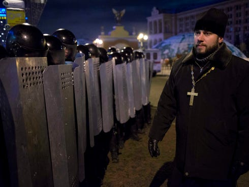 An Ukrainian priest speaks to riot police as they block Pro-European Union activists camping out in tents on the Independence Square in Kiev, the capital, on Wednesday.